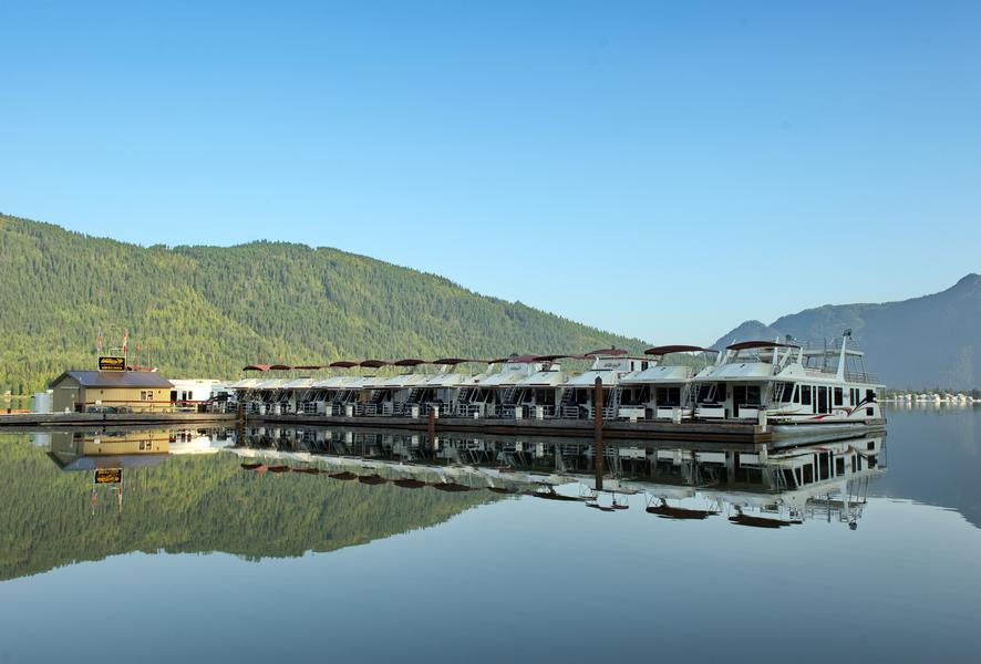 Luxurious houseboats lined up at the marina rest on pristine waters