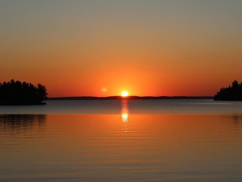 A brilliant sunset over the calm, cool waters of Rainy Lake Photos