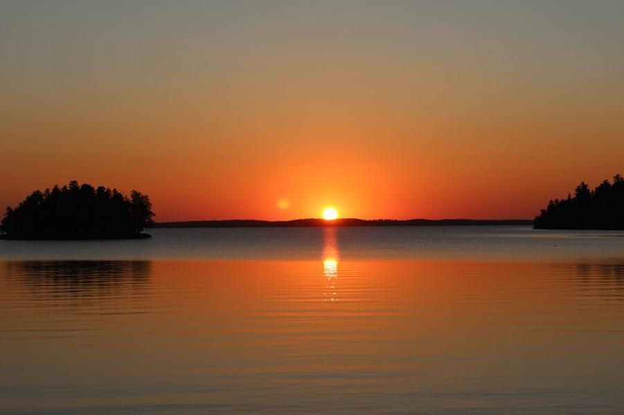 A brilliant sunset over the calm, cool waters of Rainy Lake