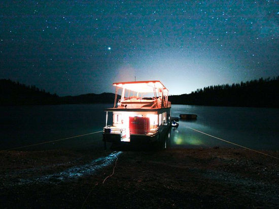 Shining lights from your houseboat illuminate against the star filled sky